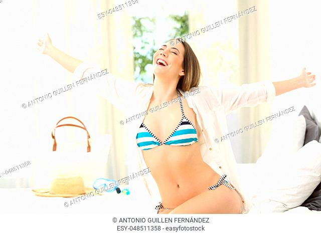 Excited hotel guest wearing bikini celebrating summer holidays spreading arms on a bed