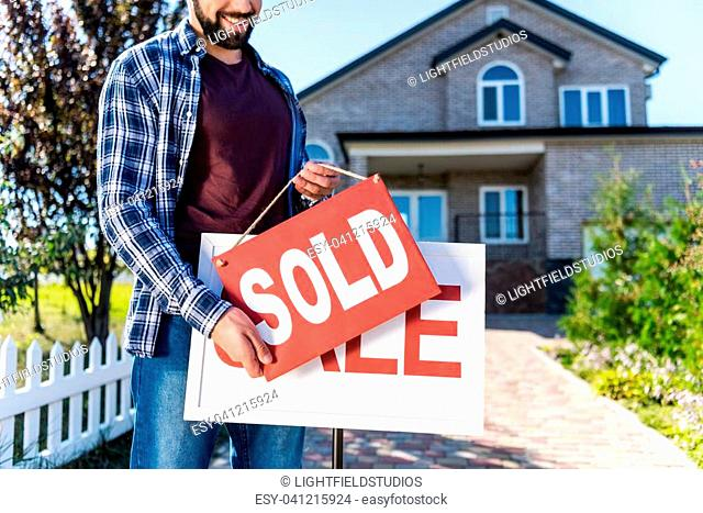man hanging sold sign in front of house