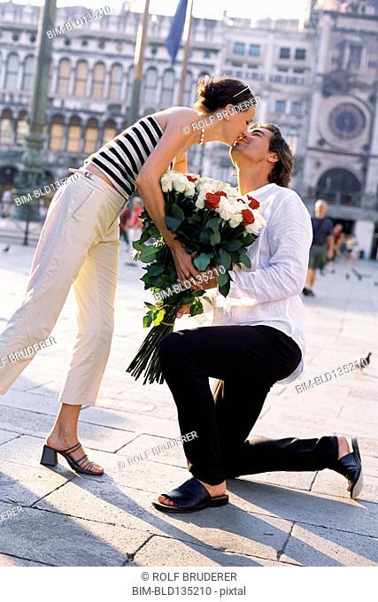 Man giving girlfriend flowers in St. Mark's Square, Venice, Veneto, Italy