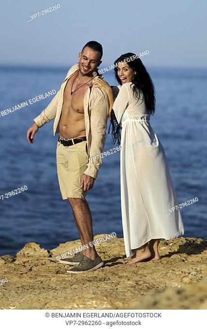 happy playful couple enjoying togetherness at Mediterranean beach. Greek ethnicity. In holiday destination Hersonissos, Crete, Greece
