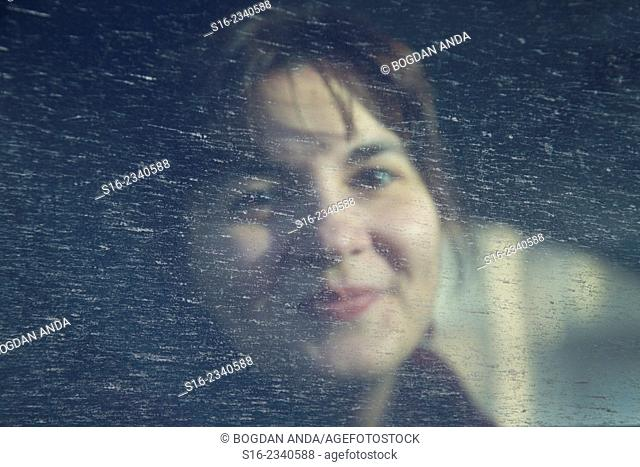 Young pretty woman smiling behind a spotted splashed car window
