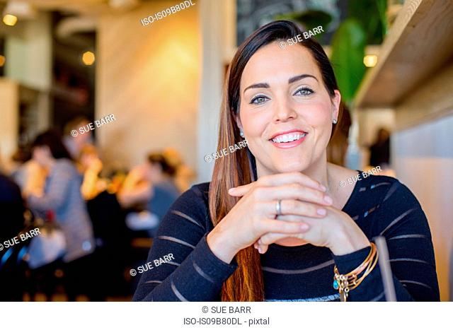 Portrait of happy woman with hands together, wearing engagement ring