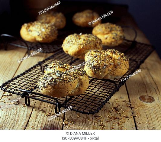 Knotted seeded bread rolls on wooden table, fresh from oven
