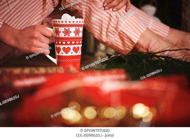 Woman holding hot chocolate in festive mug