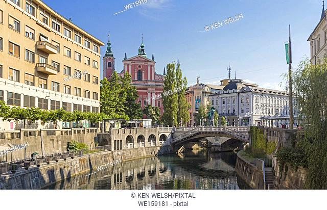 Ljubljana, Slovenia. Baroque Franciscan Church of the Annunciation seen behind the Tromostovje, or Triple Bridge on the Ljubljanica river