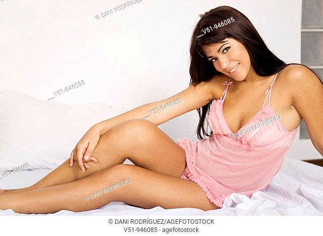 Brunette woman with lingerie posing on bed