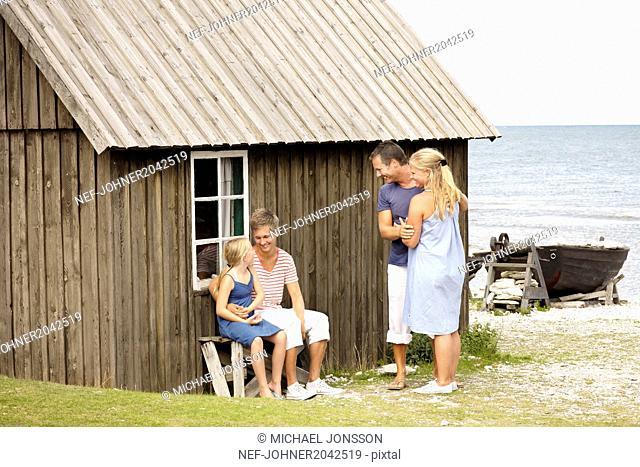 Family near wooden house at sea