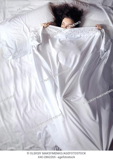 Cute young woman lying in bed covered with a bedsheet up to her eyes peeking from under a blanket