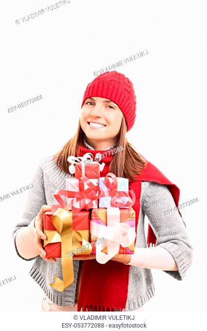 My Christmas shopping is done. Beautiful young woman in winter clothes holding wrapped presents, isolated on white background