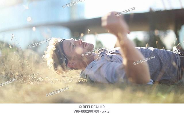 Trendy male sunbathing in long grass