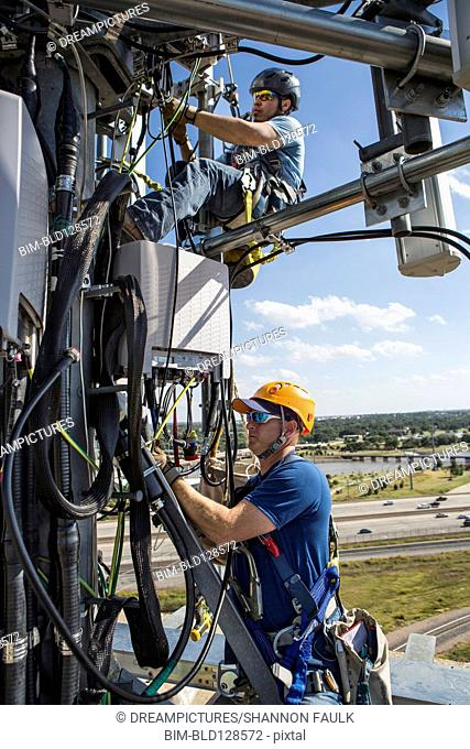 Workers harnessed to cell tower