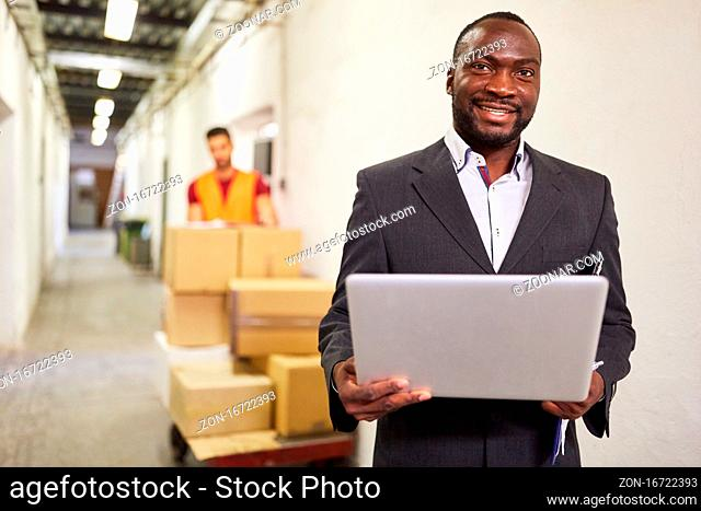 Afrikanischer Unternehmer im Warenlager mit Laptop Computer im Onlinehandel