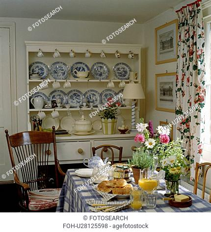 Blue+white china on cream dresser in dining room with table set for breakfast