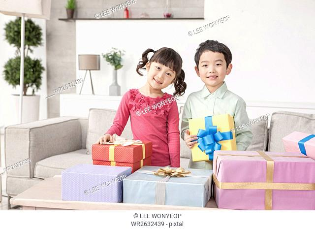 Smiling boy and girl with present boxes in living room