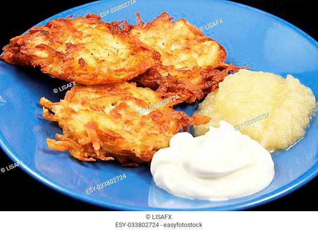 Potato latkes for Hanukkah, served with sour cream and applesauce