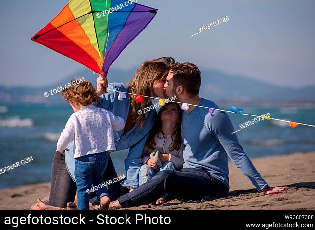 young family with kids resting and having fun with a kite at beach during autumn day