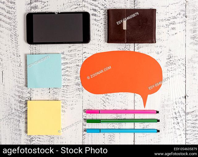 Smartphone pens blank speech bubble sticky notes wallet wooden background