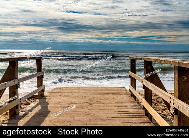 A wooden boardwalk and beach access leads directly onto beach with stormy waves and skies