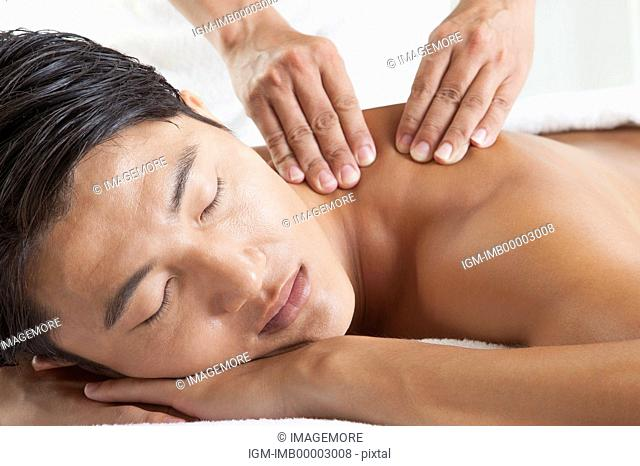Man enjoying massaging with eyes closed