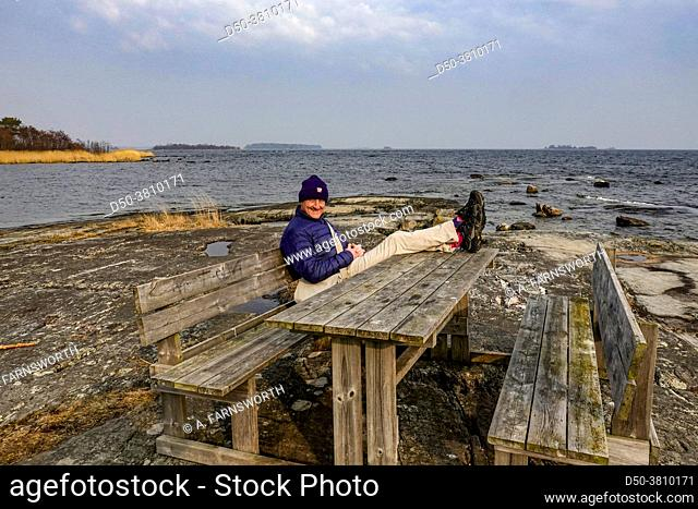 Ljustero, Sweden A man sits at a picnic table beside the Baltic Sea on an island in the Stockholm archipelago