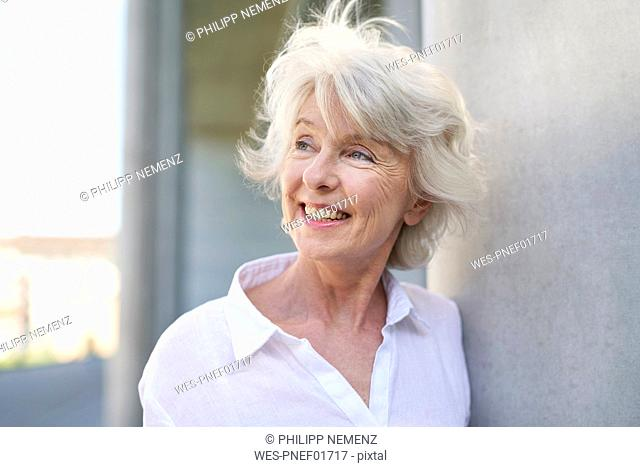 Portrait of happy mature woman with blowing hair