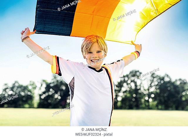 Boy, enthusiastic for soccer world championship, waving German flag