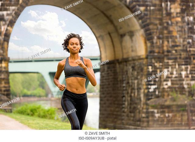 Woman wearing spandex jogging by bridge