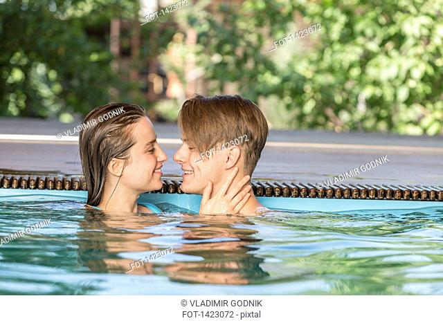 Side view of passionate couple smiling in swimming pool