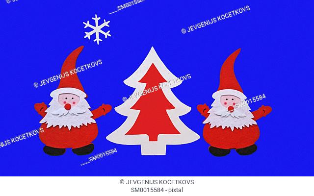 Drawing of Santa Claus and Christmass tree made of glued pieces of felt and plywood on a blue background, hand-made
