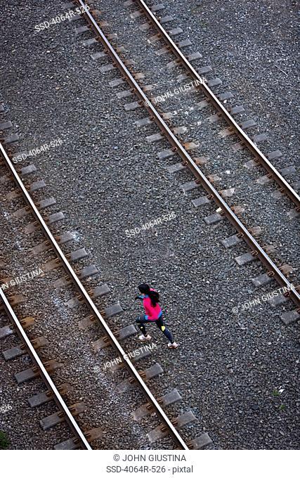 Woman running across railroad tracks