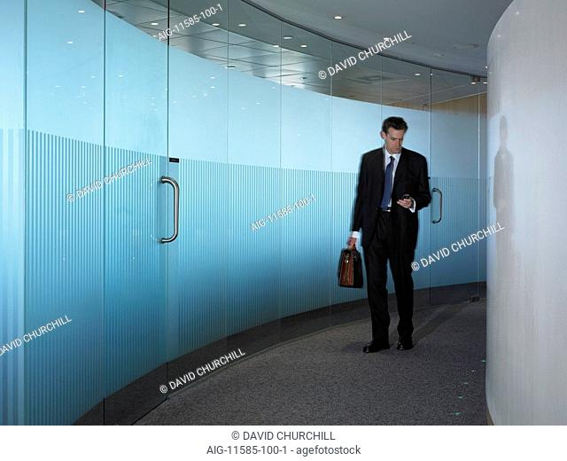 Office life and interiors (model released). Businessman in corridor using mobile phone about to leave