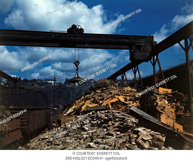 Recycling scrap steel during World War II at the Allegheny Ludlum Steel Corporation in Brackenridge, Pennsylvania. An overhead magnet deposits the scrap in a...