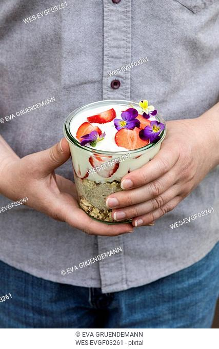 Man's hands holding glass of granola with natural yogurt, strawberries and Horned Violets