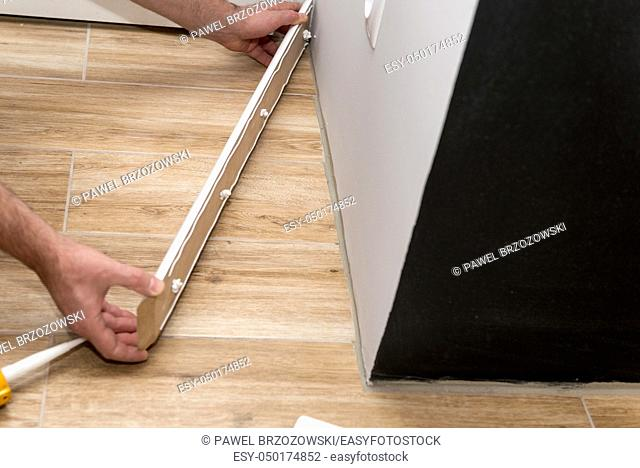 Close up of mans hands installing skirting board