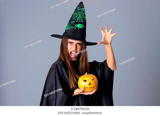 Young beautiful woman in black costume of witch with black hat holding a pumpkin and showing anger on blue background in studio