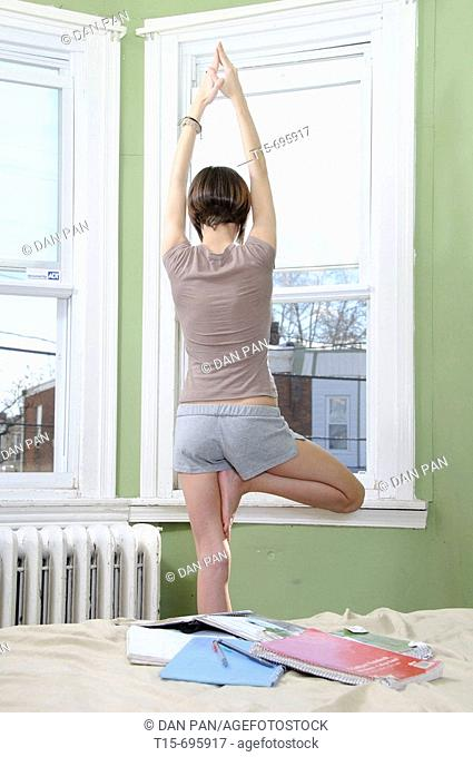 Young woman practice yoga by the window