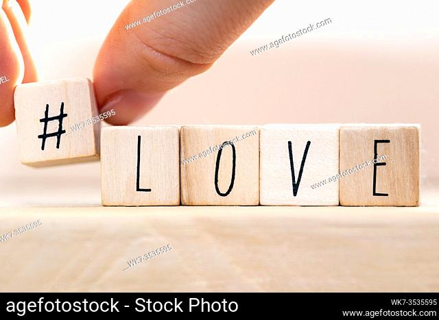 Word Love on wooden cubes with Hashtag, close-up near white background valentine concept
