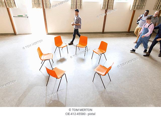 Men arriving, approaching chairs in circle in community center