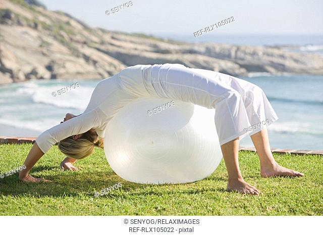 Mature woman doing Pilates exercises with exercise ball ocean in background