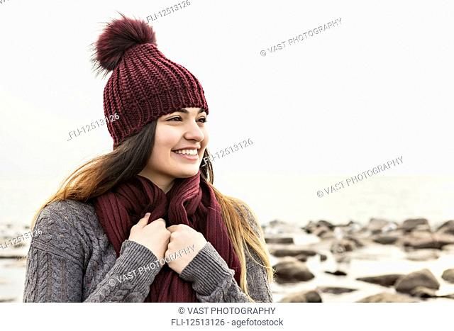 Girl standing on a beach in autumn wearing a knit hat and scarf, Woodbine Beach; Toronto, Ontario, Canada