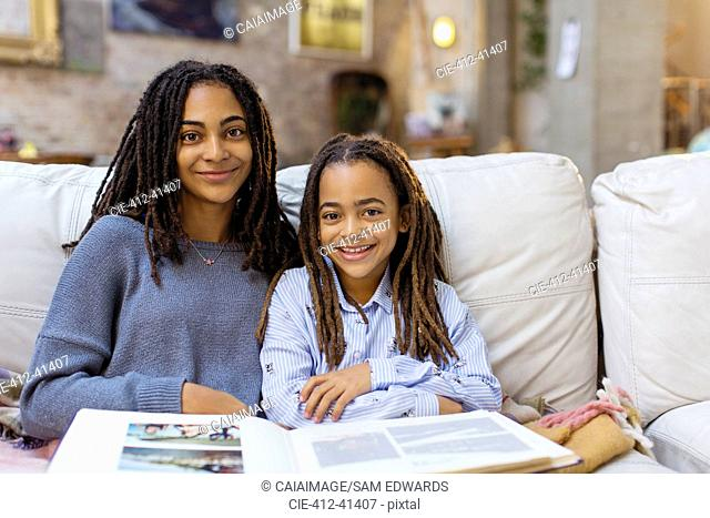 Portrait smiling, confident sisters with photo album on sofa