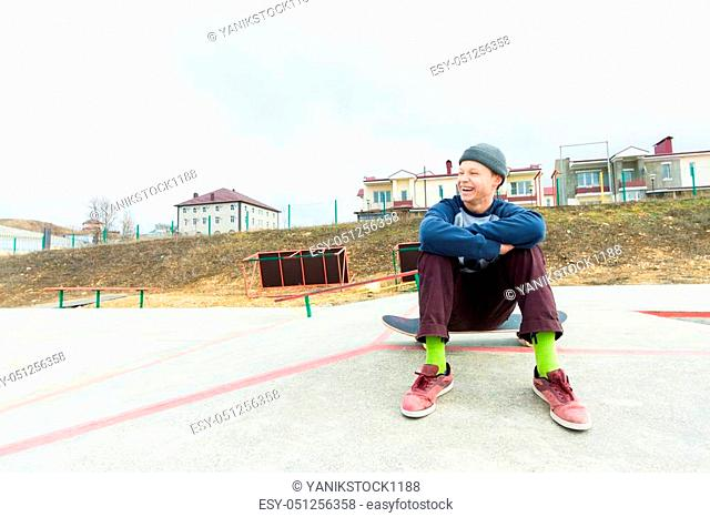 A teenage boy is sitting on a skateboard in the park and smiling. The concept of free time pastime for teenagers in the city