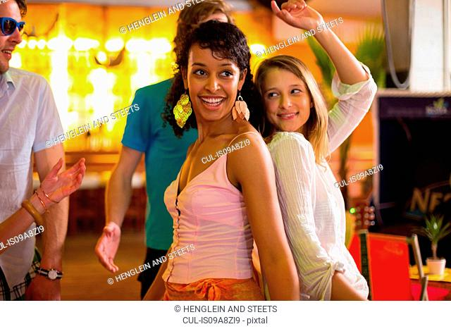 Two females dancing back to back in bar