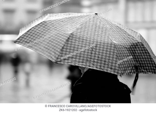 A woman walks under the rain in front of the Basilica of Saint Mary of Flower in Florence, Italy