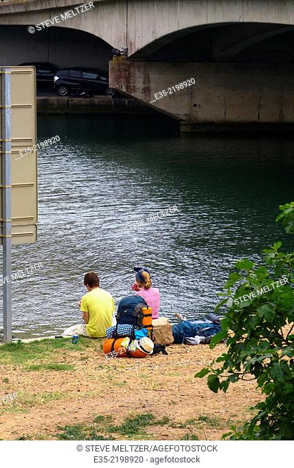 A couple eats lunch along the Herault river at Agde, France