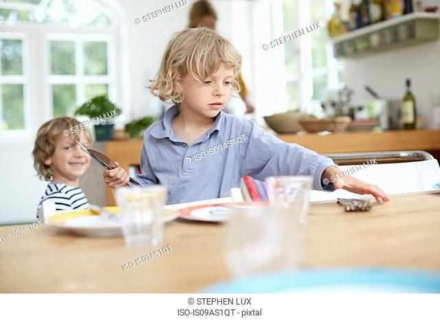 Boy setting table in kitchen