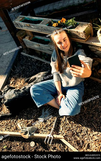 Happy young woman with dog in garden taking a selfie