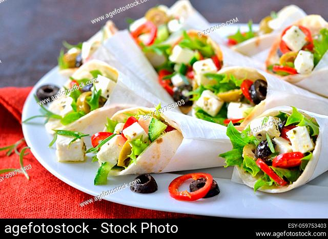 Mini-Tortillas gefüllt mit griechischem Bauernsalat mit Fetakäse sowie grünen und schwarzen Oliven - Mini wraps stuffed with Greek farmers salad with feta...