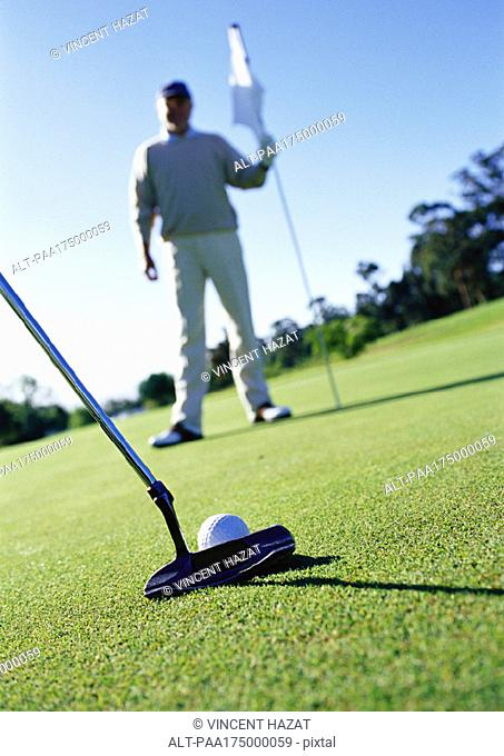 Golfer holding flag on green, putter and ball in foreground