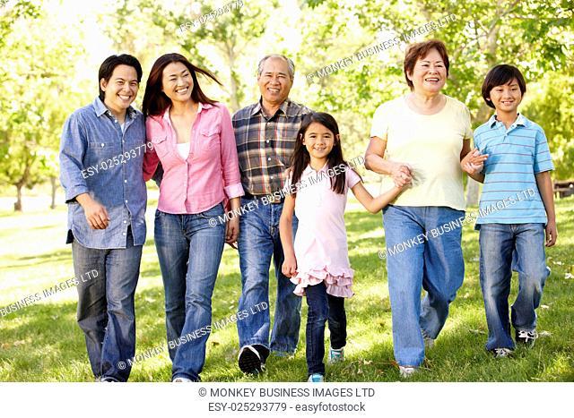 Multi-generation Asian family walking in park